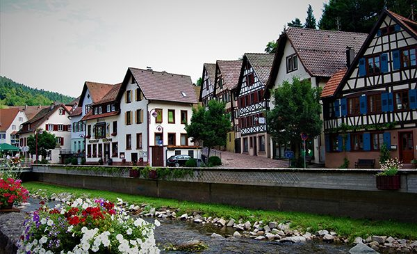 A street of typical Germanic style homes in front of a small flower-lined brook. Public domain image.