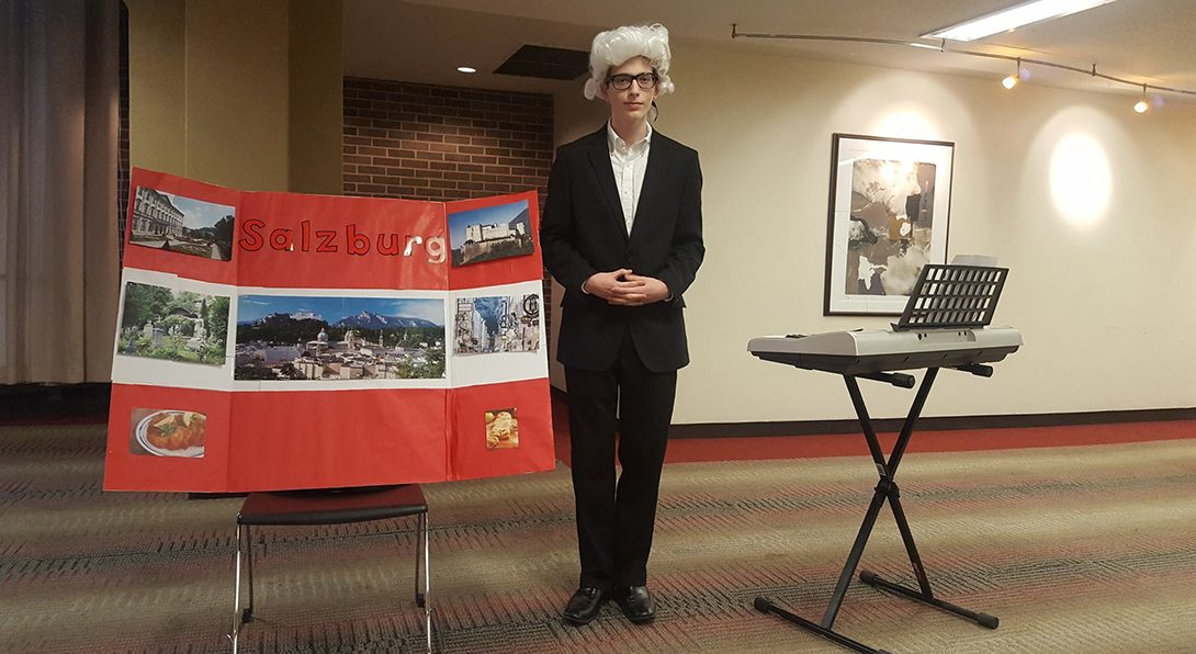 A high school student dressed in a Mozart wig stands next to a keyboard and a poster presenting Salzburg.