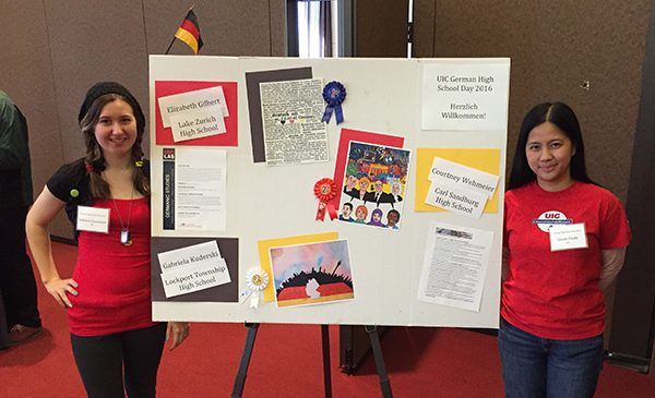 Two female judges stand in front of a student poster from German High School Day