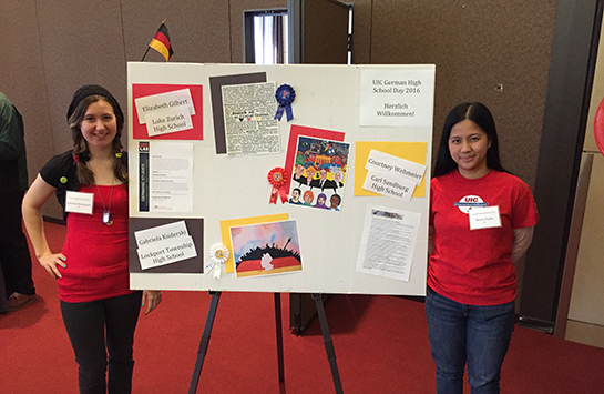 Two female judges stand next to a student poster entry.