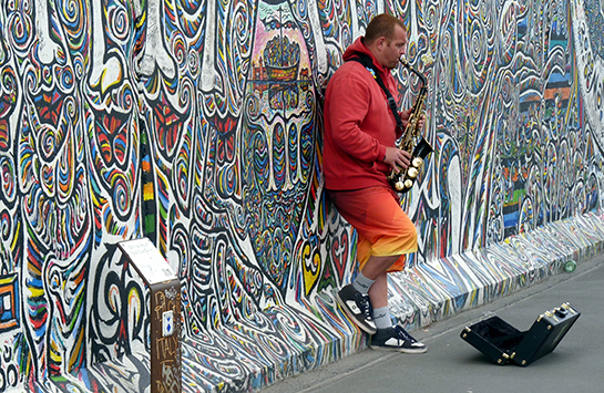 A street musician plays saxophone while leaning against a heavily graffitied wall.