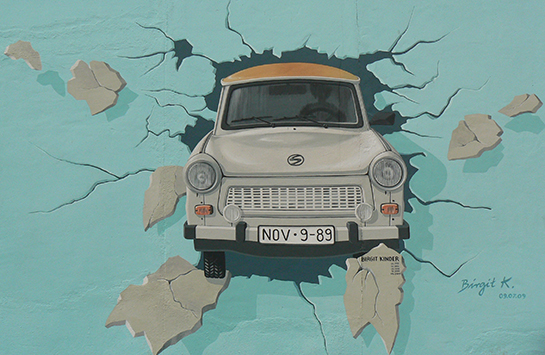 Graffiti of a car crashing through a wall. Painted on the Berlin Wall.