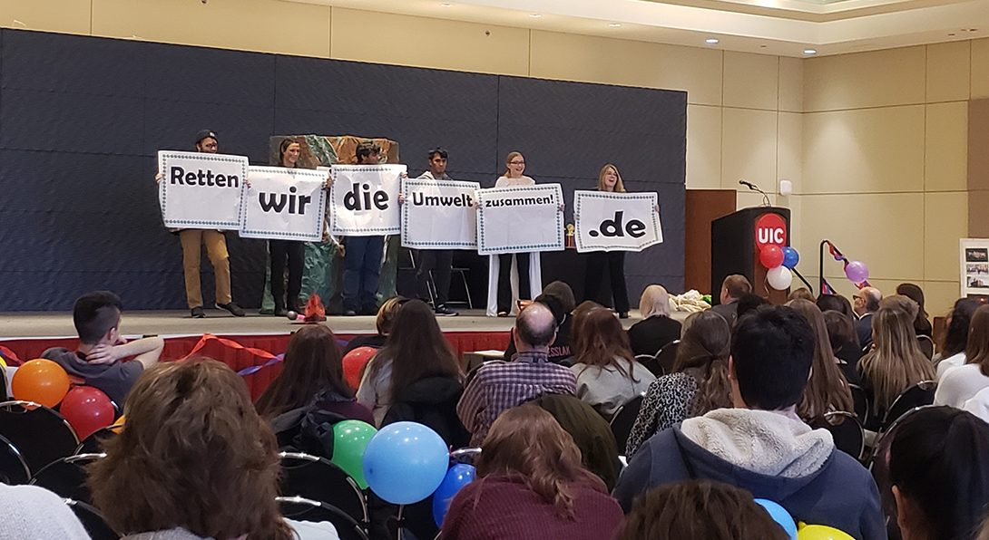 a mixed group of students stand on a stage before a mixed audience holding signs spelling out the sentence